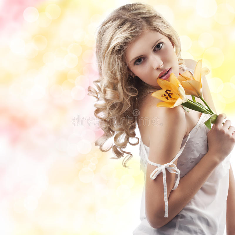Blond curly woman holding lily stock photo