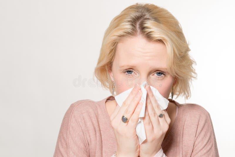 Blond dam Pressing Tissue på hennes näsa med kopieringsutrymme royaltyfri fotografi