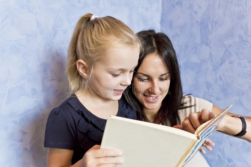 Blond daughter with brunette mother. Cute smiling daughter are reading a book with her mother royalty free stock photography