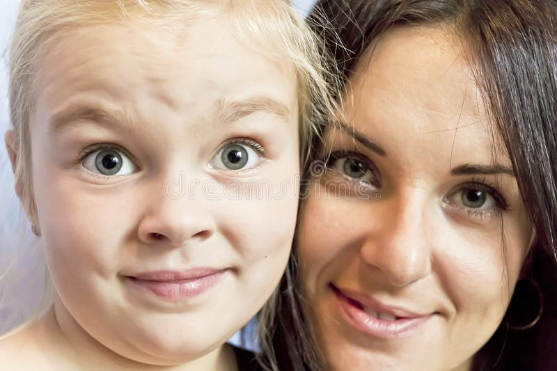 Blond daughter with brunette mother. Portrait of cute blond daughter with brunette mother stock photos