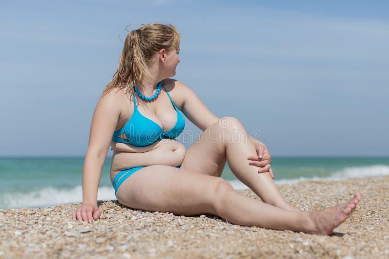 Blond de poids excessif à la mer photo stock