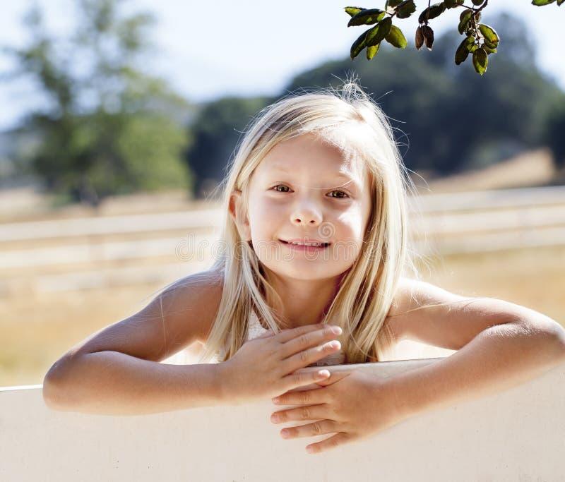 Blond dziewczyna na gospodarstwa rolnego ogrodzeniu zdjęcia stock