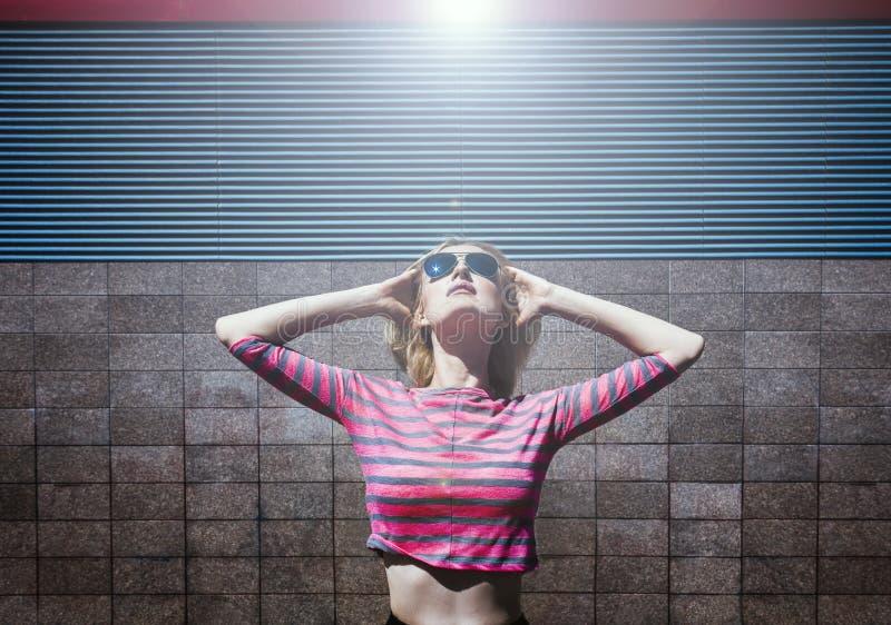 Blond dziewczyna pozuje w menchiach paskował bluzki i słońca szkła, przyglądających z głową i rękami rzucającymi z powrotem up Dz obraz royalty free