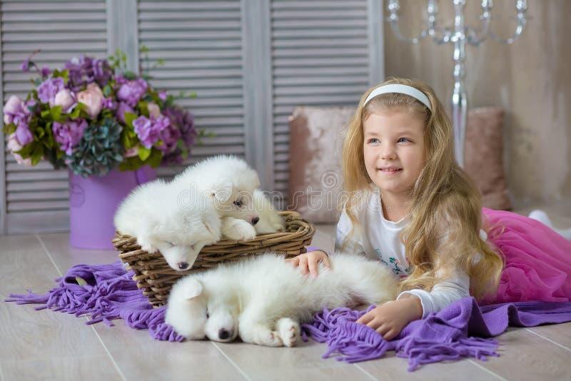 Blond dziewczyna pozuje z łuskowatego szczeniaka białym kolorem w retro pracownianym krótkopędzie Śliczna młode dziecko sztuka z  obrazy stock