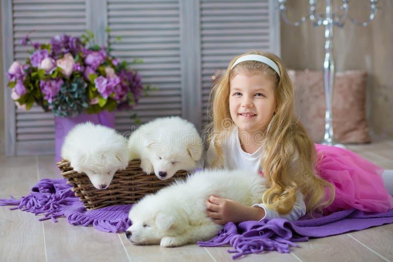 Blond dziewczyna pozuje z łuskowatego szczeniaka białym kolorem w retro pracownianym krótkopędzie Śliczna młode dziecko sztuka z  fotografia royalty free