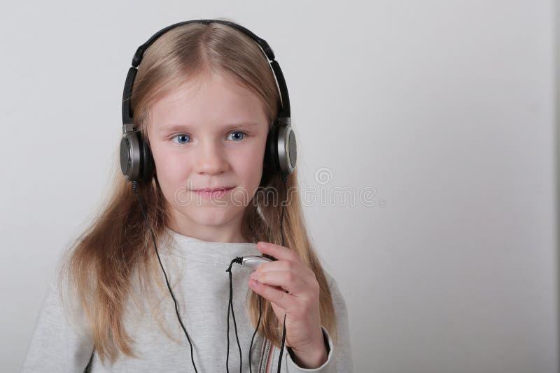 Blond dziewczyna słucha muzykę i śpiew z hełmofonami Śliczna mała dziewczynka robi rolce podpisywać zdjęcia stock