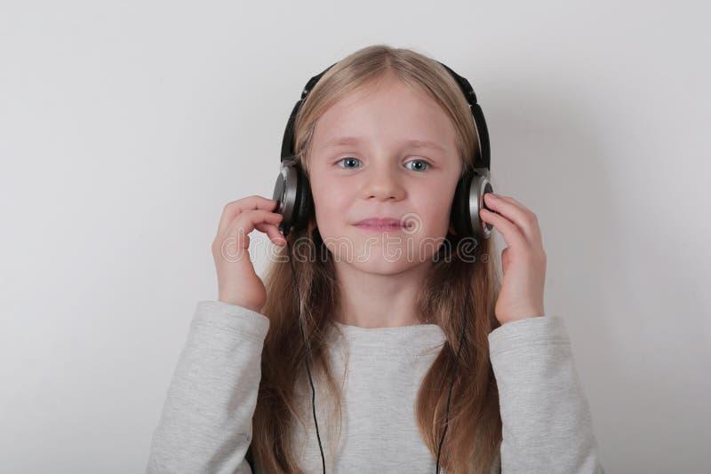 Blond dziewczyna słucha muzykę i śpiew z hełmofonami Śliczna mała dziewczynka robi rolce podpisywać obrazy stock