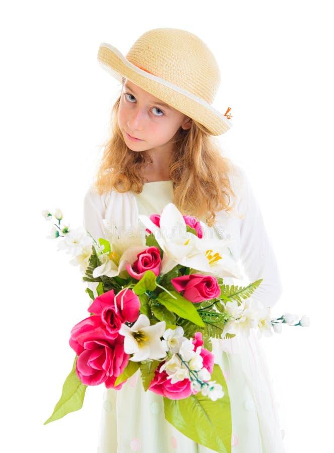Blond dziewczyna w bielu smokingowym i słomianym kapeluszu z bukietem kwiaty obraz stock