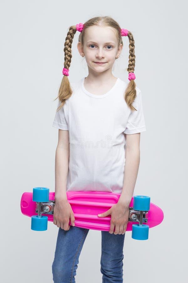 Blond dziewczyna z Ładnymi Pigtails Pozuje Z Różowym Pennyboard obrazy stock