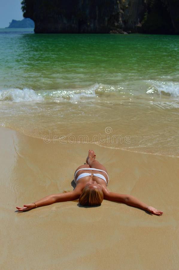 Blond dziewczyny lying on the beach sunbathing na plaży obrazy royalty free