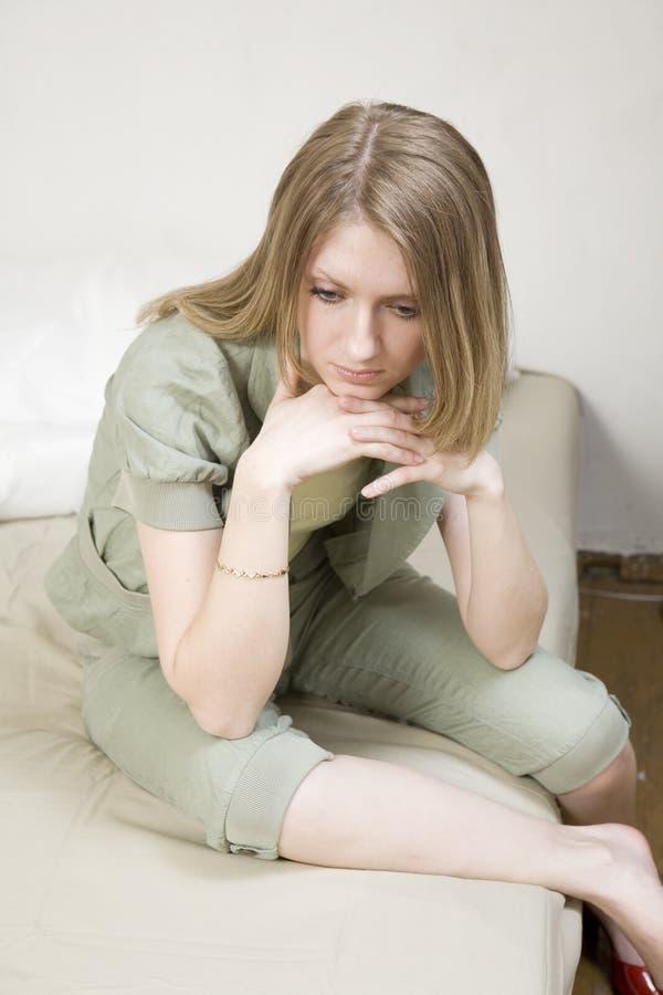 blond eftertänksam sittande kvinna för underlag arkivbilder
