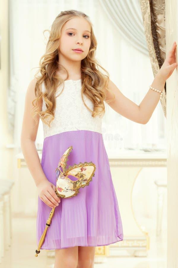 Blond elegancka dziewczyna pozuje z maską w rękach zdjęcie royalty free