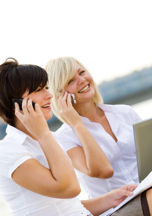 Blond en brunett? meisjes die telefonisch spreken stock foto