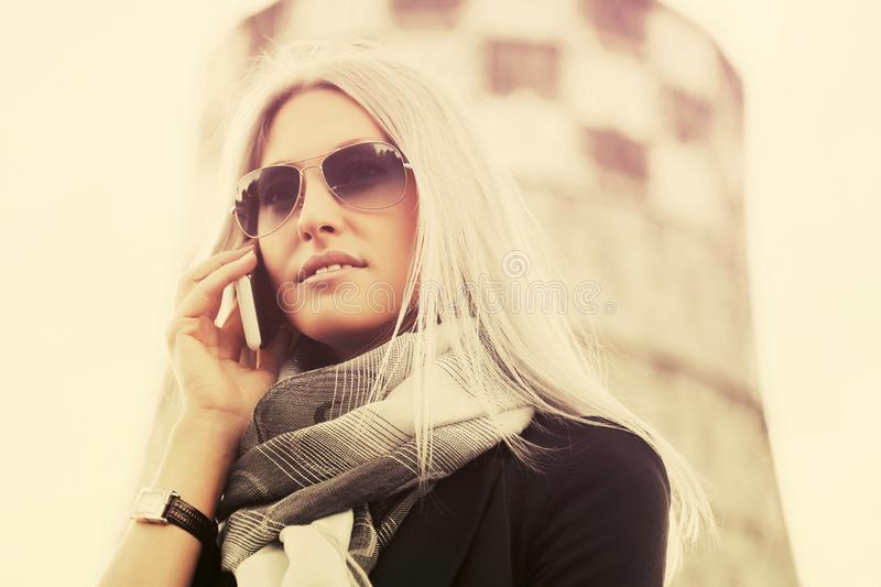 Blond fashion business woman in sunglasses using cell phone outdoor. Blond business woman in sunglasses using cell phone walking outdoor Stylish fashion model royalty free stock image