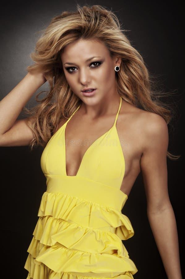 Blond fashion model wearing yellow dress royalty free stock image