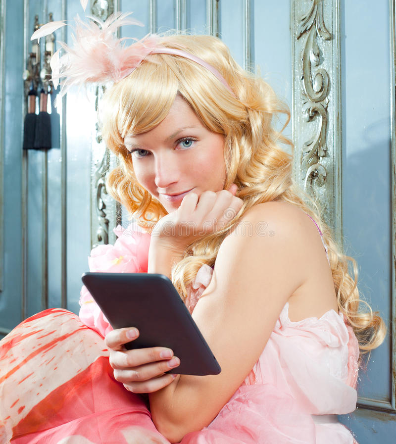 Blond fashion princess woman reading ebook tablet. With retro spring pink dress royalty free stock photos