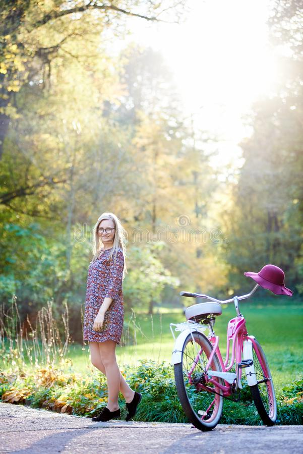 Blond fashionable long-haired attractive girl in short dress with lady bicycle in sunny park. royalty free stock photography