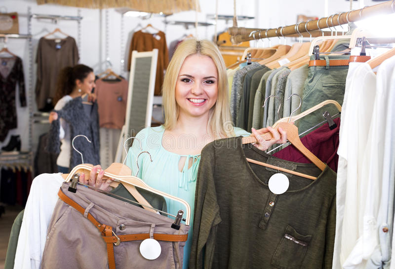 Blond female customer selecting new garments. Cheerful blond female customer selecting new garments at the store royalty free stock photos