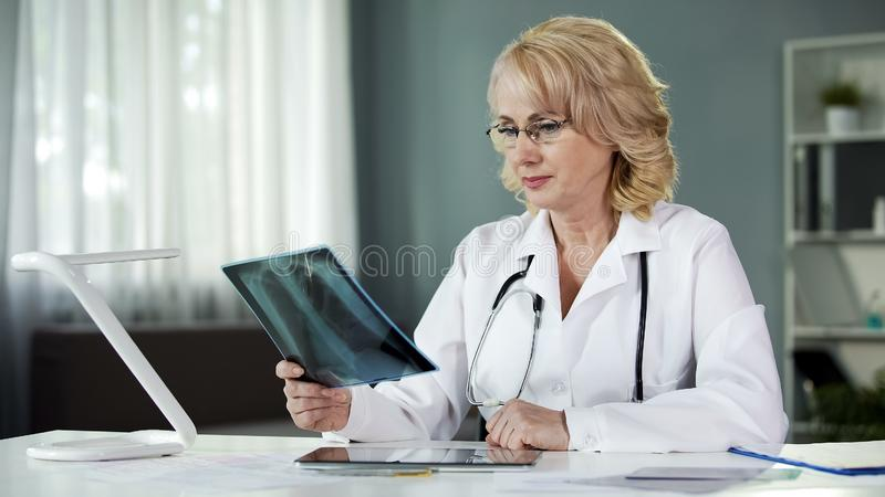 Blond female doctor examining X-ray picture, medical profession, diagnosis. Stock photo stock photography