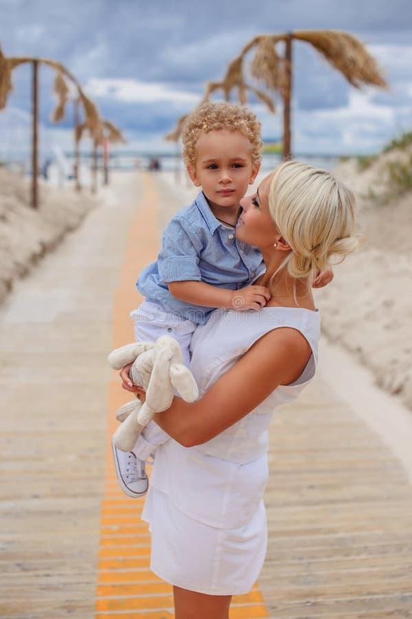 Blond female holding child. stock photos
