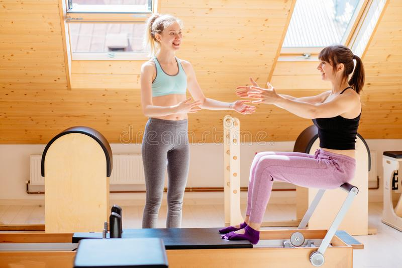 Blond female instructor consulting female client workout pilates on reformer practice in pilates studio, working out stock photo