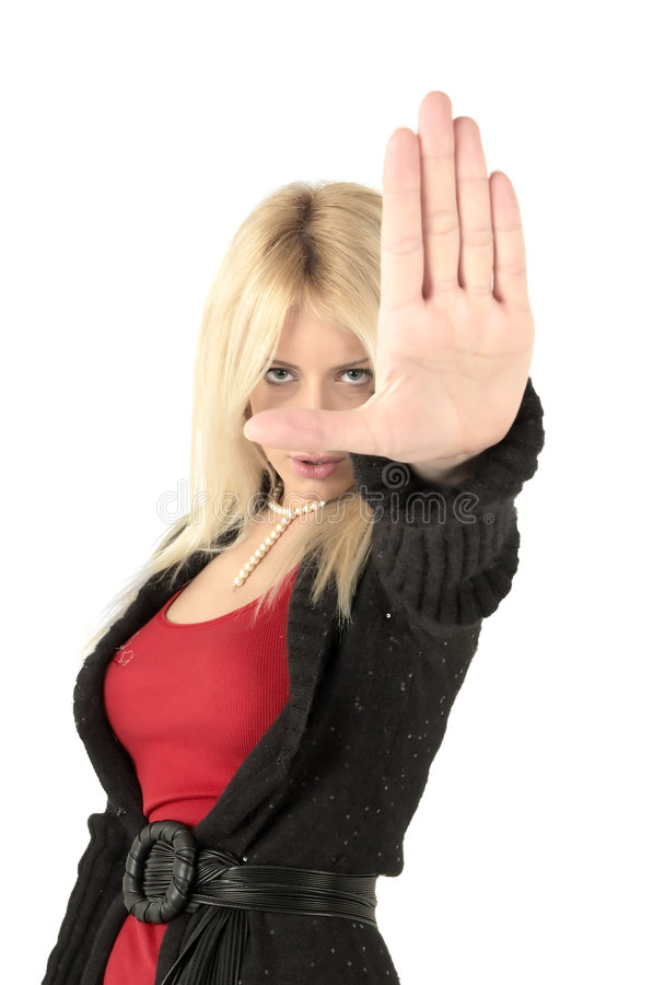 Blond Female Stop Sign. Young blond adult female with arm outstretched and hand palm out in a stop command stock photo