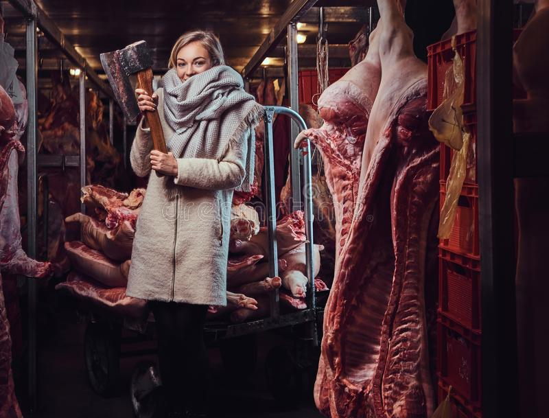 Blond female in a warm jacket in a meat freezer storage. Blond female in a warm jacket holds an ax in a meat freezer storage stock photo