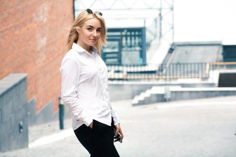 Blond flicka för affär med telefonen royaltyfri bild