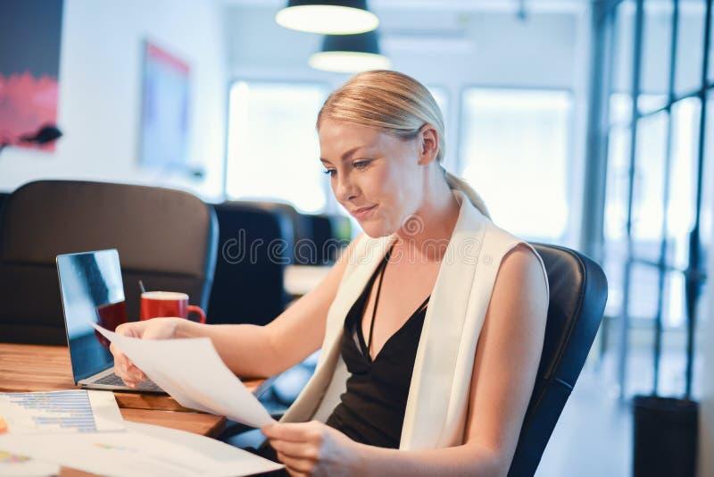 Blond flicka för affär som tänker om arbete och läsning en affär royaltyfria foton