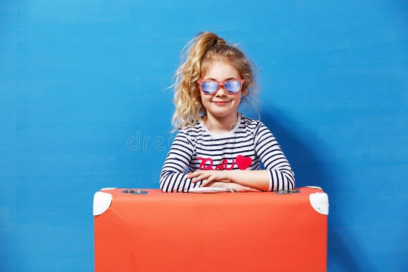 Blond flicka för barn med den rosa tappningresväskan som är klar för sommarsemester Lopp- och affärsföretagbegrepp royaltyfri bild