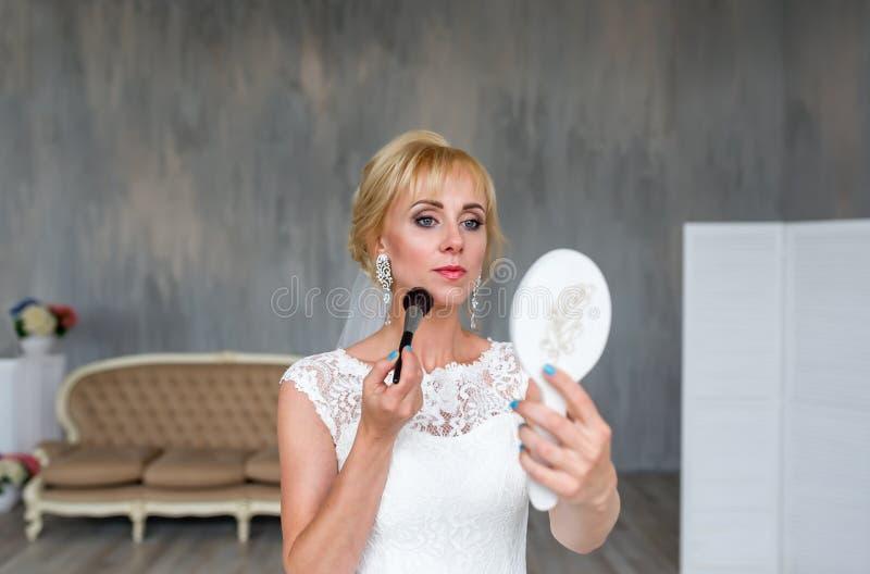 Blond flicka för härlig brud i bröllopsklänning med frisyren och ljus makeup på hem- bakgrund som ser i spegeln arkivbild