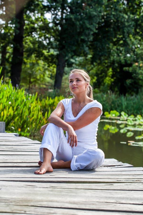 blond flicka för 20-tal som utomhus drömmer i den avslappnande solen royaltyfria bilder