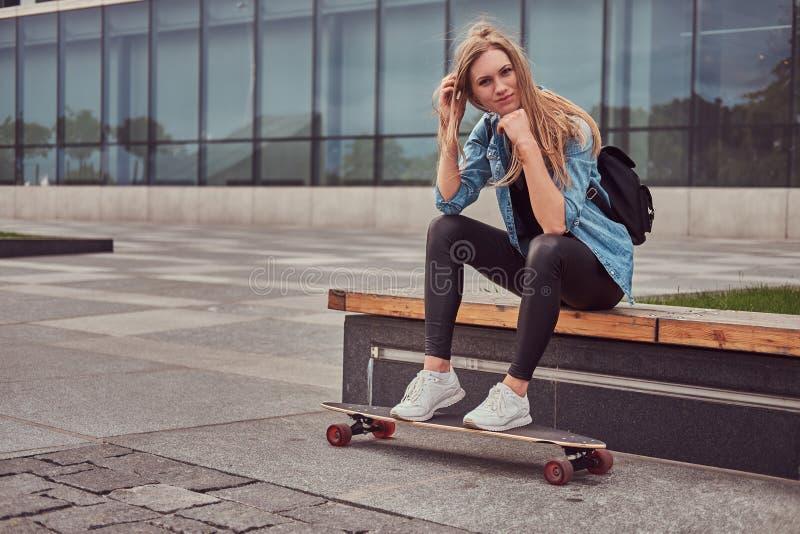 Blond flicka för ung hipster i tillfällig clothessitting på en bänk mot en skyskrapa som vilar, når att ha ridit på skateboarden royaltyfri fotografi