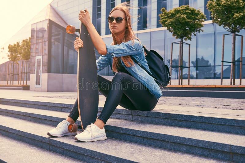 Blond flicka för ung hipster i tillfällig kläder och solglasögon som sitter på moment mot en skyskrapa som vilar, når att ha ridi royaltyfri fotografi