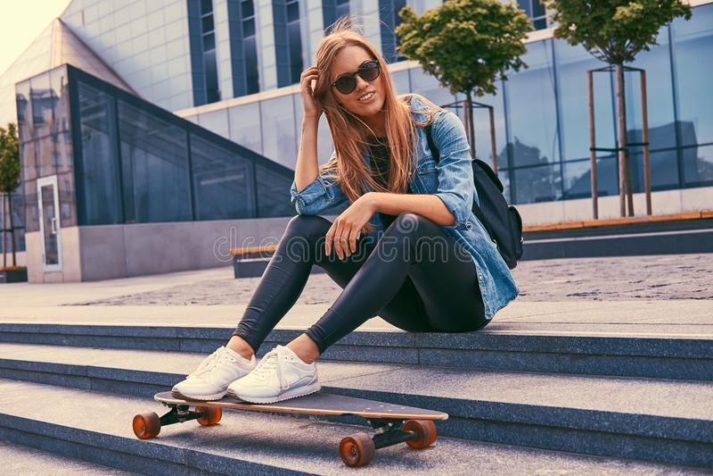 Blond flicka för ung hipster i tillfällig kläder och solglasögon som sitter på moment mot en skyskrapa som vilar, når att ha ridi royaltyfria foton