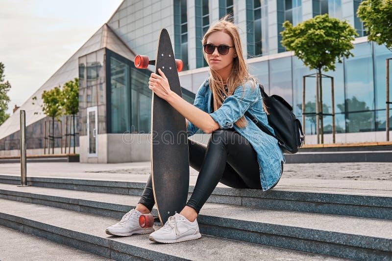 Blond flicka för ung hipster i tillfällig kläder och solglasögon som sitter på moment mot en skyskrapa som vilar, når att ha ridi arkivfoton