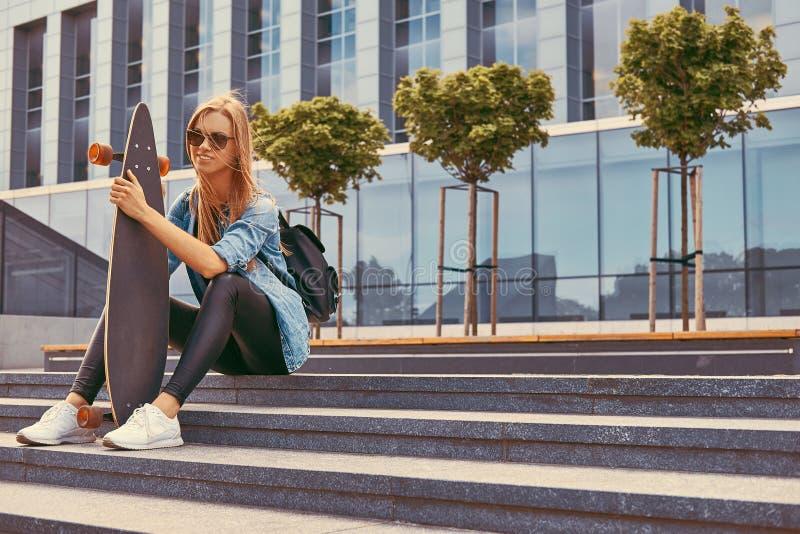 Blond flicka för ung hipster i tillfällig kläder och solglasögon som sitter på moment mot en skyskrapa som vilar, når att ha ridi fotografering för bildbyråer