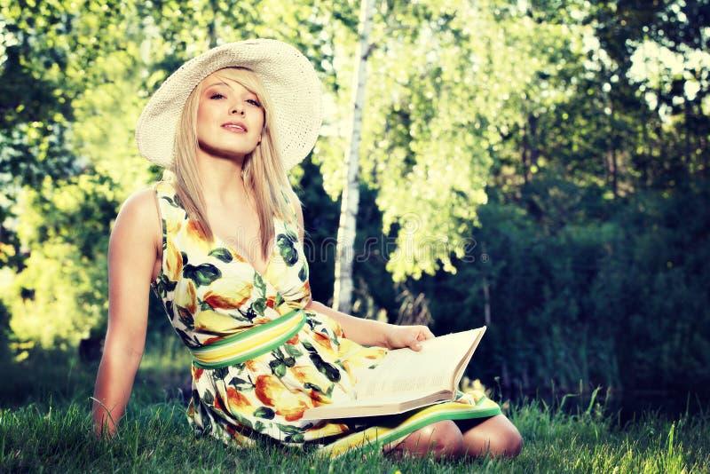 Blond flicka för ung kvinna med hatten som kopplar av i en parkeraläsebok som bara sitter på gräs royaltyfri fotografi