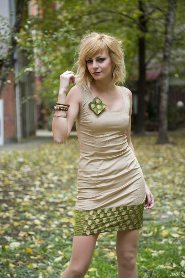 Blond flicka f?r attraktiv modekl?nning som poserar i omgivning f?r stil f?r h?stsidor fallande fotografering för bildbyråer