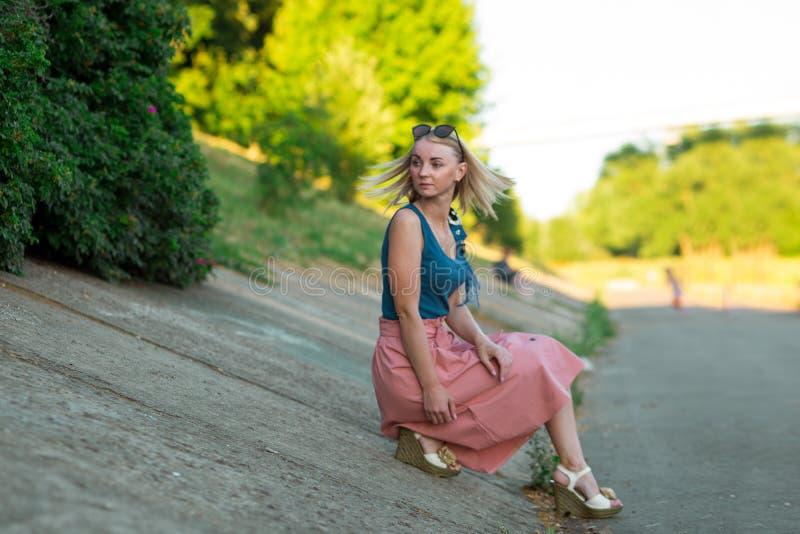 Blond flicka i blå bästa och ljust - rosa kjol som bort sitter på lutningen av vägyttersidan, blick hår i rörelse parkerar in fotografering för bildbyråer