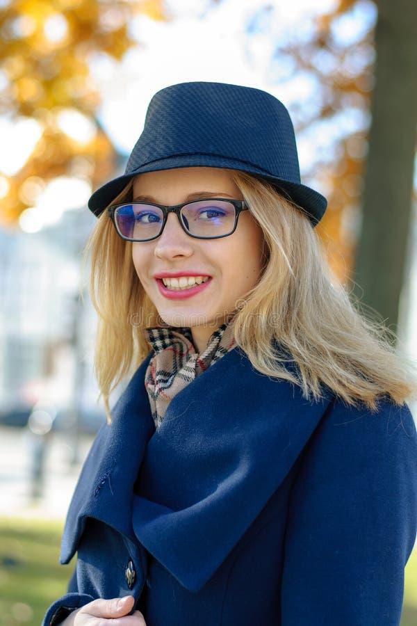 Blond flicka i blått le för hatt royaltyfria foton