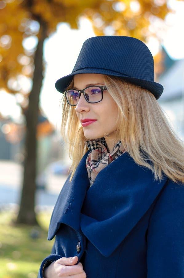 Blond flicka i en blå hatt som ser till sidan royaltyfria bilder