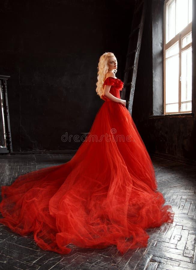 Blond flicka i en lyxig klänning arkivfoton