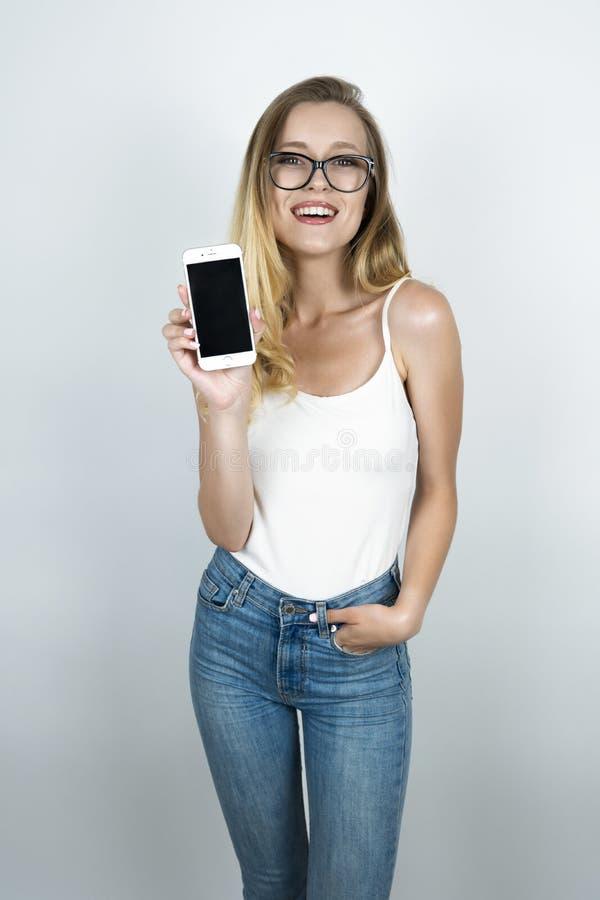Blond flicka i exponeringsglas som rymmer smartphonen som ler isolerad vit bakgrund royaltyfri foto