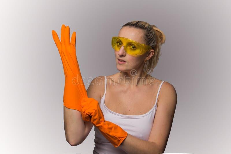 Blond flicka i orange handskar och skyddande exponeringsglas royaltyfria bilder