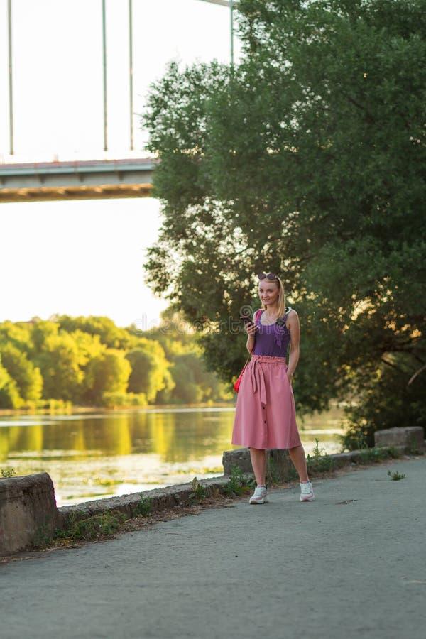 Blond flicka i purpurfärgad överkant och ljust - rosa kjol i gymnastikskor med små röda leenden för en skuldrapåse 100f 2 8 28 f? royaltyfri fotografi