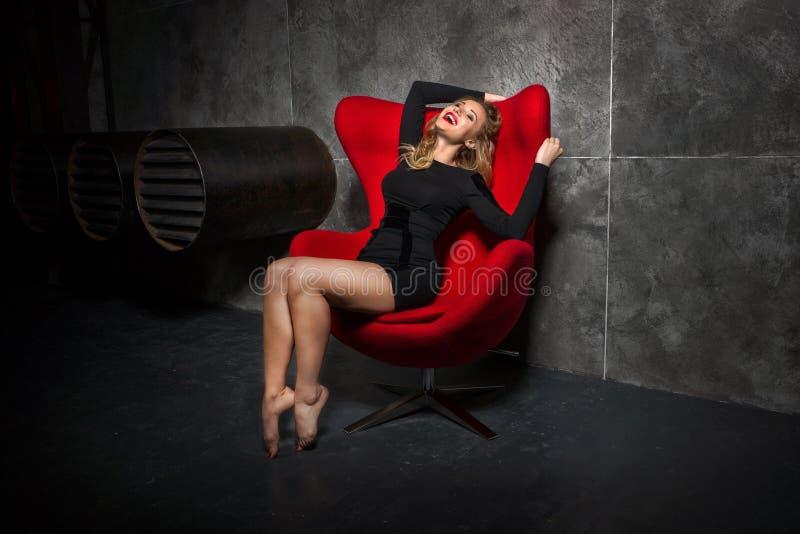 Blond flicka i svart klänningsammanträde på den röda fåtöljen royaltyfria foton