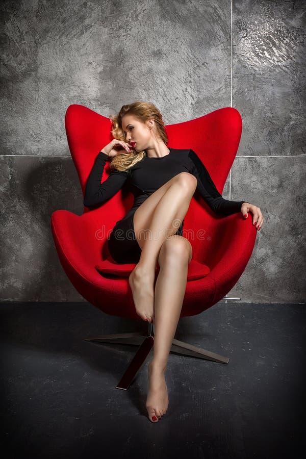 Blond flicka i svart klänningsammanträde på den röda fåtöljen arkivbild
