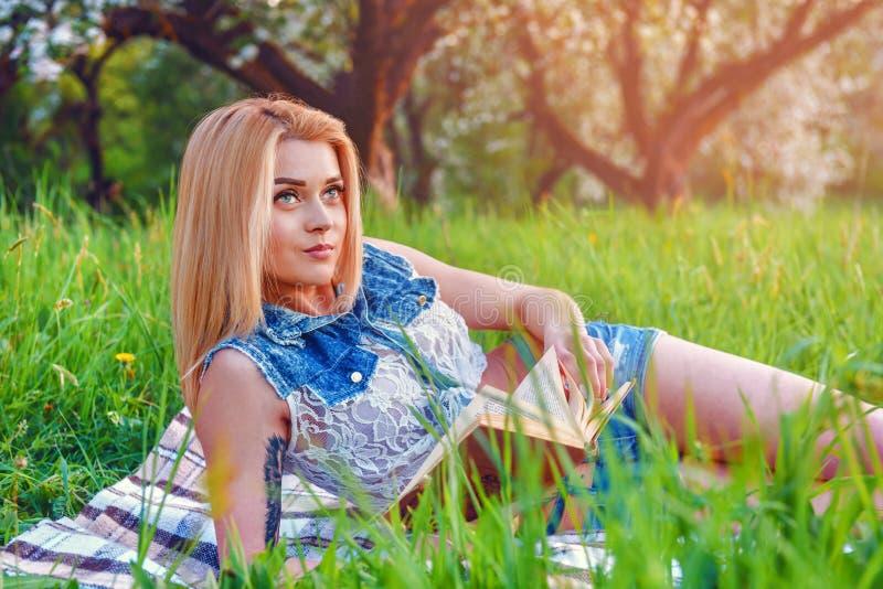 Blond flicka läst bok på grönt gräs royaltyfri bild