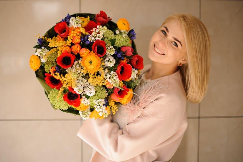Blond flicka med att förbluffa buketten med vallmo royaltyfri fotografi